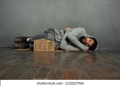 homeless man sleeping on the floor, sign for help