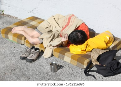 homeless man sleeps on a filthy mattress under a dirty blanket on the street of the city metropolis