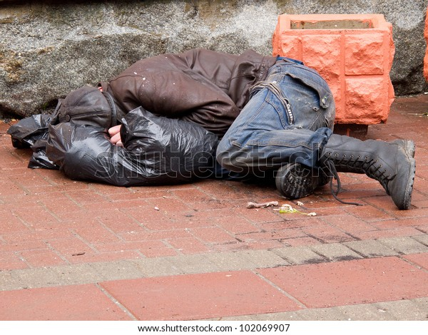 Homeless man sleeps on a pavement