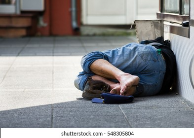 Homeless man sleeps on the street in the shadow of the building.