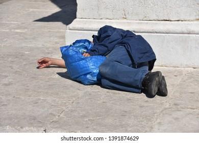 A homeless man sleeps in the street in broad daylight