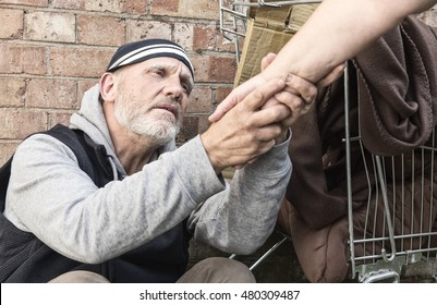 Homeless man taking an unrecognizable woman's hand