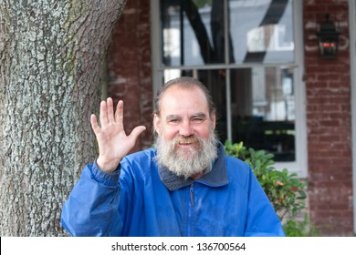 Homeless man waving while outdoors during the daytime.