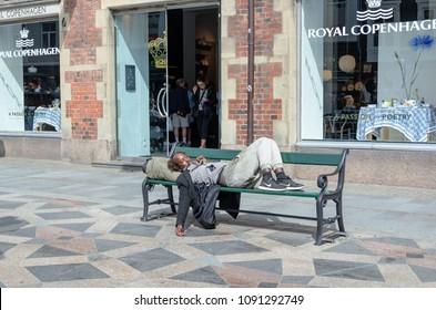 homeless men sleeping on bench in Copenhagen, Denmark, July 2017