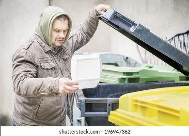 Homeless near garbage container with opened food box