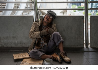 Homeless old man or beggar sitting on city walk and getting painful from heart attack. Poverty and Sickness. Social issue concept.