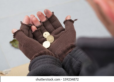 Homeless person holding a few cents in his hands