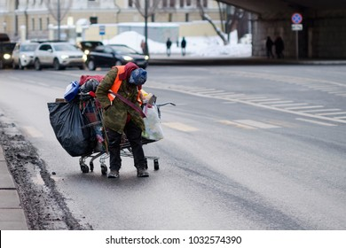 A homeless person on the road, a cart with things