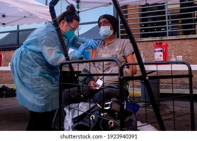 A homeless person receives a COVID-19 vaccine from a nurse at a vaccination clinic set up in the parking lot of the L.A. Mission in Los Angeles, Wednesday, Feb. 24, 2021.