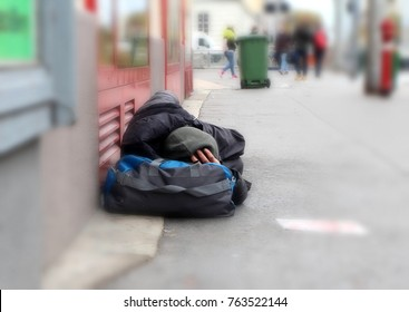 Homeless person sleeping on the street in front of a shop in a big city.