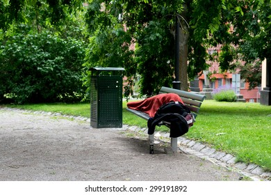 Homeless person sleeping in park, on bench. Stockholm, Sweden.