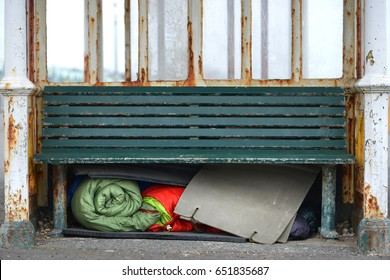 Homeless person's sleeping bags and bedding under a bench