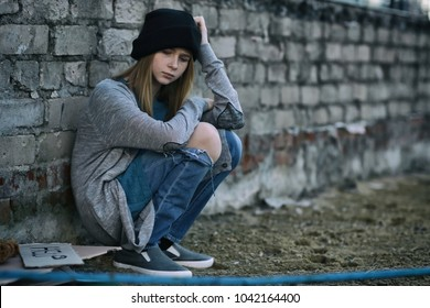 Homeless poor teenage girl sitting near brick wall outdoors