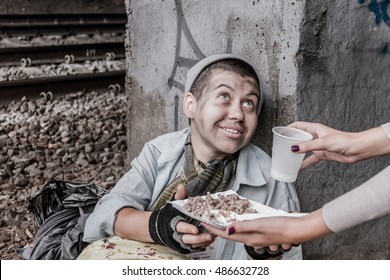 Homeless poor woman being handed food by volunteer and smiling
