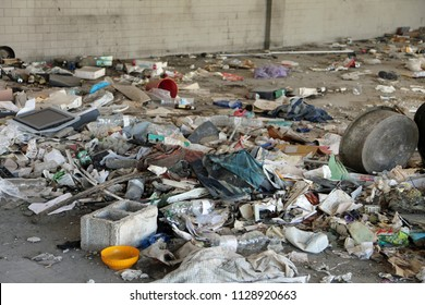 homeless shelter without people and many broken objects and dirty rags
