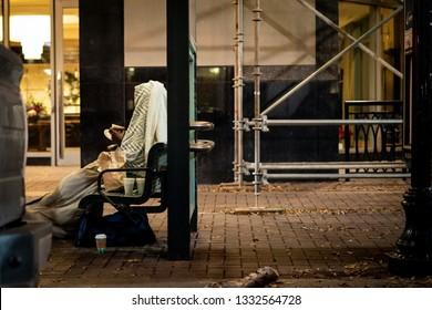 Homeless sitting on bench eating under blanket in city