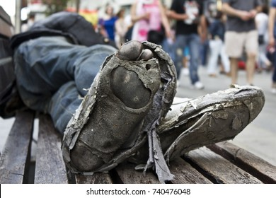Homeless man´s sleeping in a bench with rotten and dirty feet crossed with destroyed shoes from a low angle close shot with unfocused people walking as background