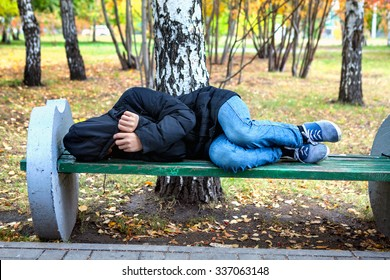 Homeless Teenager sleep on the Bench in the Autumn Park