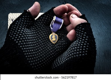 Homeless veterans and social issues concept with grunge image of dirty hands of a homeless man wearing fingerless gloves and holding a purple heart medal