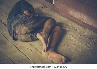 homeless or victim lay down on the floor bare foot and dirty clothes , concept for violence,beggar,poor people,homeless,A fearful child,Human Rights