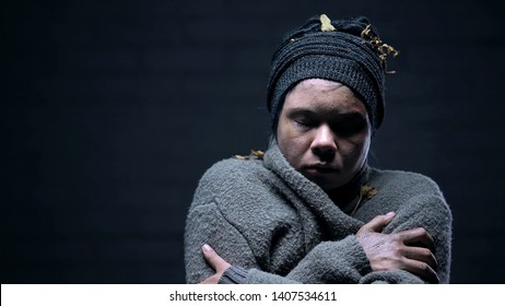 Homeless woman closed eyes suffering cold on dark background, depressed beggar