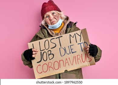 homeless woman lost her job due to coronavirus, she stands with cardboard in hands posing, isolated on pink background