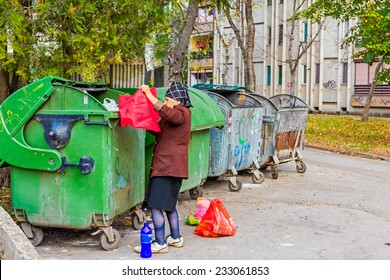 Homeless woman is searching for food in garbage dumpster/Woman in poverty/Woman is searching something in container