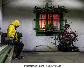 A homeless woman sits on a bench at Christmas holidays. A passenger waits for a night transport in an abandoned waiting room with Christmas decorations.
