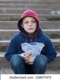 homeless young boy eats cookies