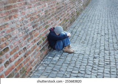 homeless young boy leaned against the wall