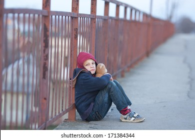 homeless young boy sitting on the bridge
