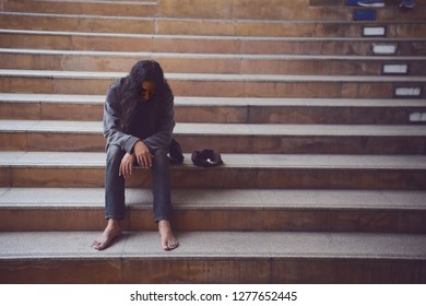 Homelessness sits on the staircase in the  middle of a large city alone the face show sad emotion and despair, Uncertainty in life, Emotioin concept.