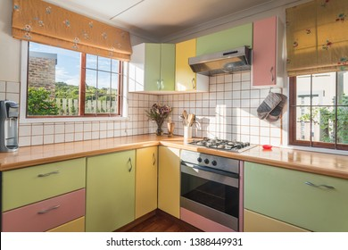 Homely Kitchen interior, with wooden counter top, green/yellow/pink cupboards, oven, stove top, windows with garden view