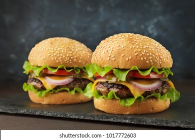 Homemad fast food: two burgers with beef, cheddar, lettuce, onion ang tomato on the slate board on dark blue background.