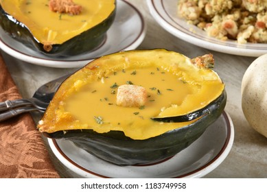 Homemade acorn or butternut squash soup served in an acorn squash shell.
