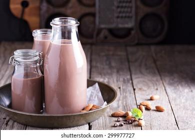 Homemade almond chocolate milk in three bottles