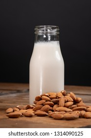 Homemade almond milk with a pile of almonds surrounding pitcher