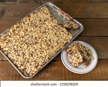 Homemade Almond Roca candy in a pan and a plate on a wood background.