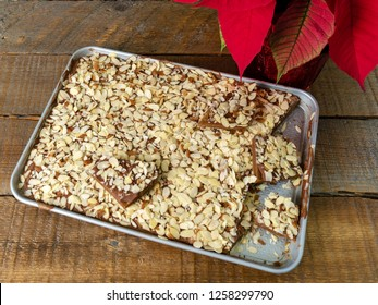 Homemade Almond Roca and a poinsettia on a wood background.