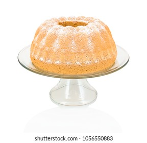Homemade Alsatian sour cream coffee cake on glass cake plate with stand isolated on white background with shadow reflection. Sweet bundt cake in german called 'Gugelhupf' or 'Bundkuchen'.