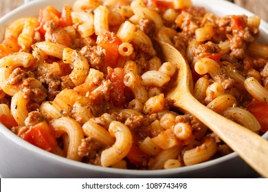 Homemade American goulash with elbow pasta, beef and tomatoes close-up in a saucepan. horizontal