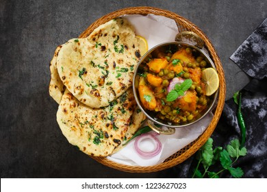 Homemade Amritsari Aloo Kulcha served with Alu Matar, top view / Indian flat bread with potato peas curry