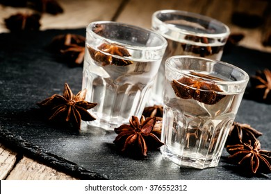 Homemade anise liqueur in a glass on a dark background, selective focus