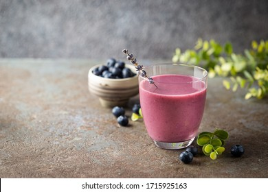 Homemade antioxidant summer blueberry smoothie in a glass on gray stone background