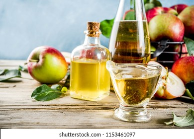 Homemade apple cider vinegar with fresh apples om wooden rustic background copy space