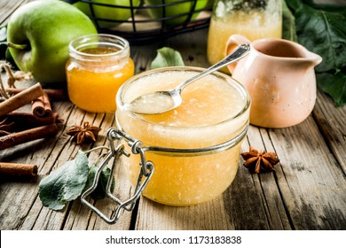 Homemade apple jam or sauce, with green apples and spices, wooden rustic background copy space