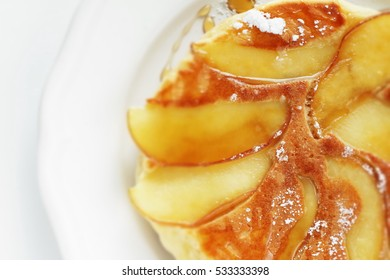 Homemade apple pancake with maple syrup