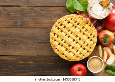 Homemade apple pie with lattice top and ingredients for cooking on wooden table. Traditional American seasonal pastry concept with copy space.