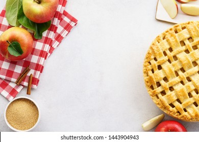 Homemade apple pie with lattice top and ingredients on gray table. Traditional American seasonal pastry background. Copy space.