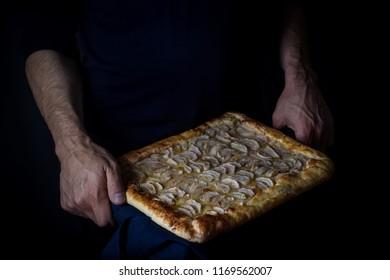 Homemade apple pie in mans hands. Dark tones,selective focus.